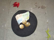 gold coins in a cap, asking for help